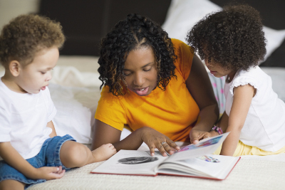 mom reading book to two children